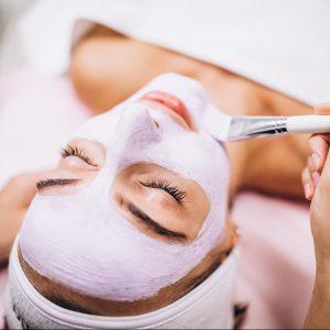 esthéticienne masque visage avec pinceau